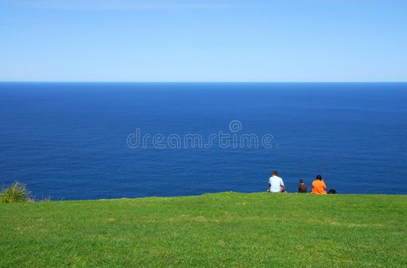Famiglia che si siede sul Headland fotografia stock