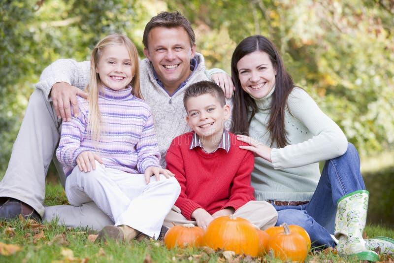Famiglia che si siede sull'erba con sorridere delle zucche immagine stock