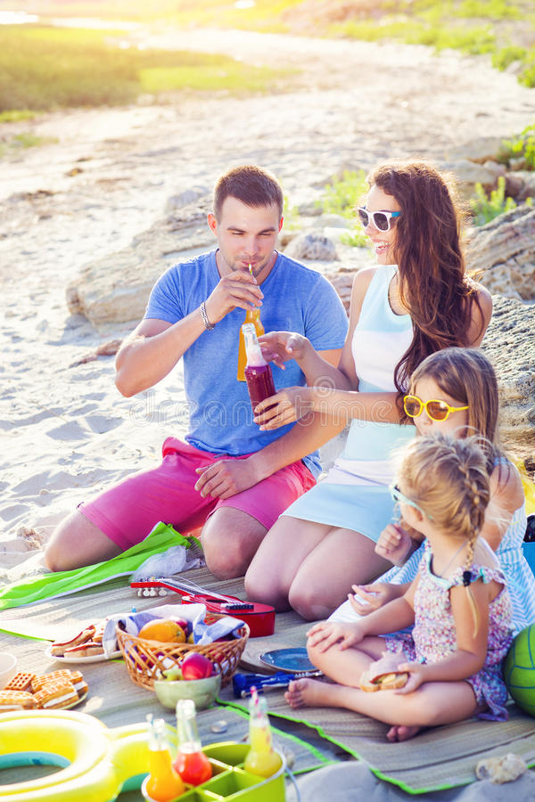 Famiglia che si siede sulla sabbia alla spiaggia al picnic di estate fotografia stock