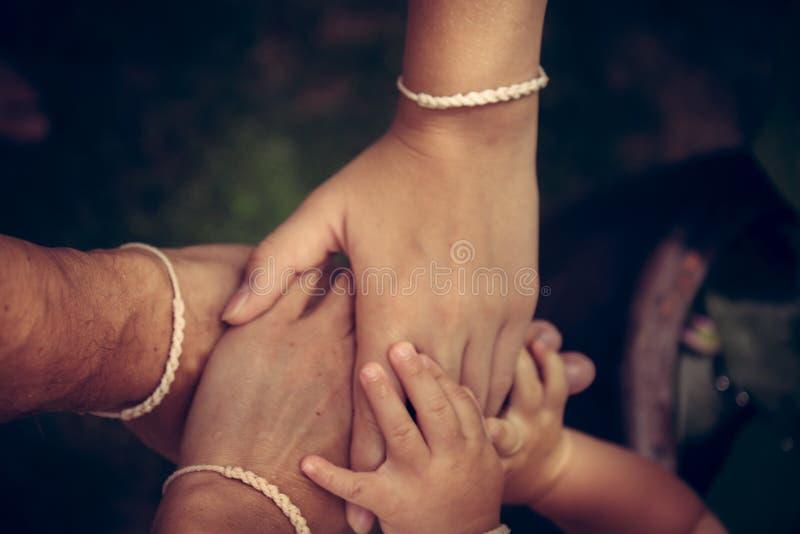 Famiglia che si tiene per mano insieme Unità del gruppo della famiglia di concetto immagini stock