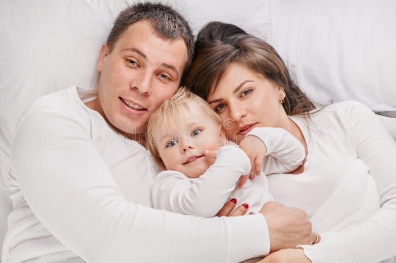 Famiglia che si trova insieme sul letto fotografia stock libera da diritti