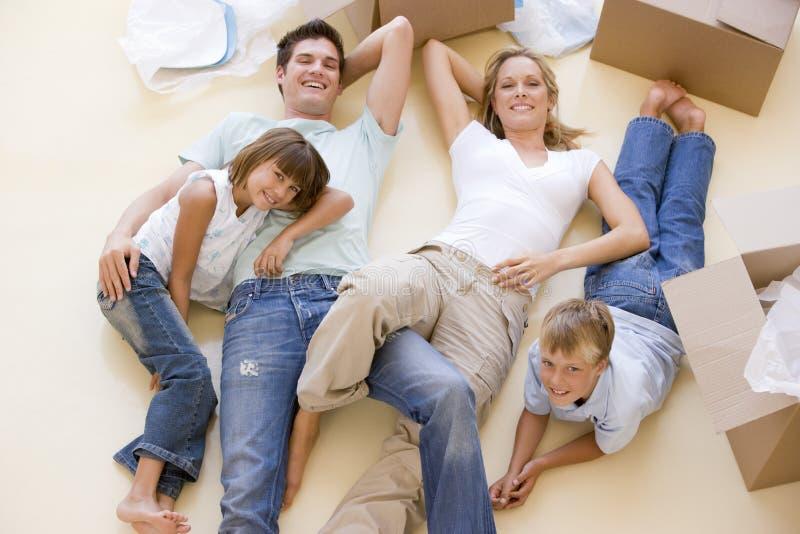 Famiglia che si trova sul pavimento dalle caselle aperte nella nuova casa fotografie stock libere da diritti