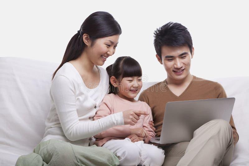Famiglia che sorride insieme e che si siede sul sofà che esamina computer portatile, colpo dello studio fotografia stock libera da diritti