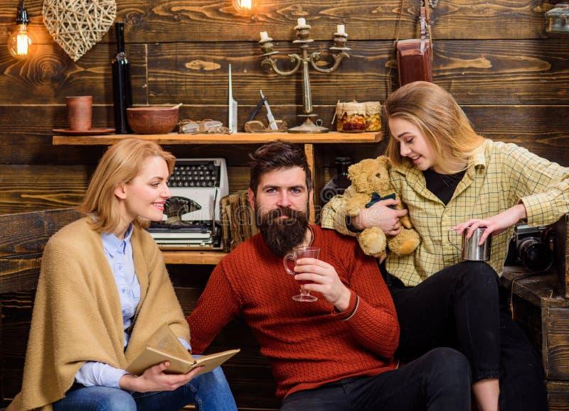 Famiglia che spende sera adorabile nella campagna Libro di lettura della donna mentre il suoi marito e figlia bevono il tè handso fotografie stock libere da diritti