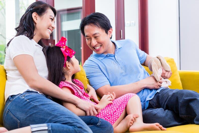 Famiglia cinese che gioca con la figlia sul sofà fotografia stock libera da diritti