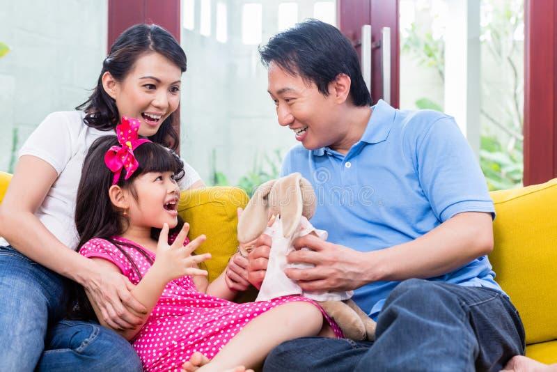 Famiglia cinese che gioca con la figlia sul sofà fotografie stock