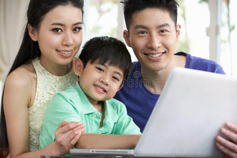 Famiglia cinese che si siede per mezzo del computer portatile nel paese fotografie stock libere da diritti
