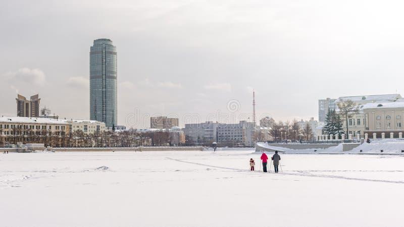 Famiglia con corsa con gli sci del bambino un giorno di inverno nuvoloso sullo stagno congelato della città fotografie stock