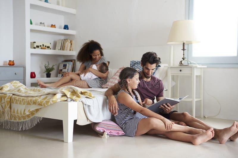 Famiglia con fare da baby-sitter in libro di lettura della camera da letto immagine stock libera da diritti