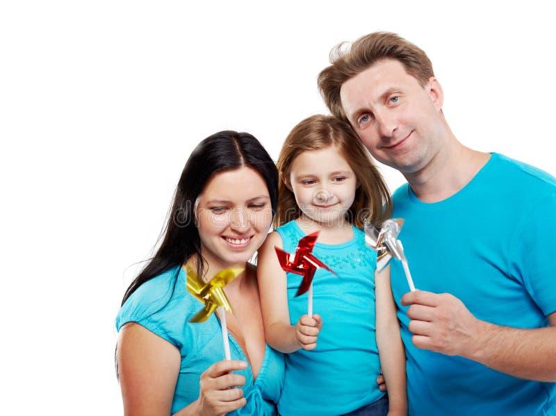 Famiglia con i mulini a vento in loro mani. fotografie stock
