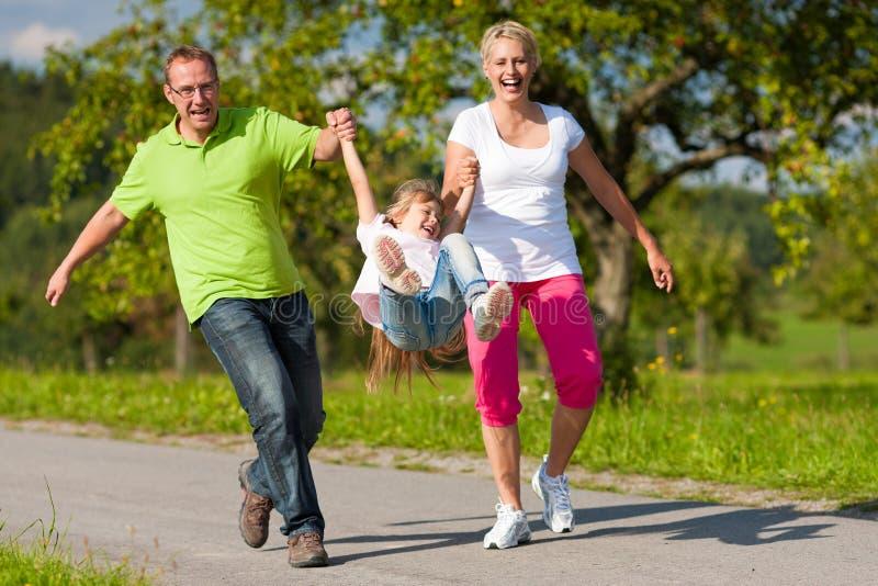 Famiglia con il bambino che ha camminata in estate immagini stock