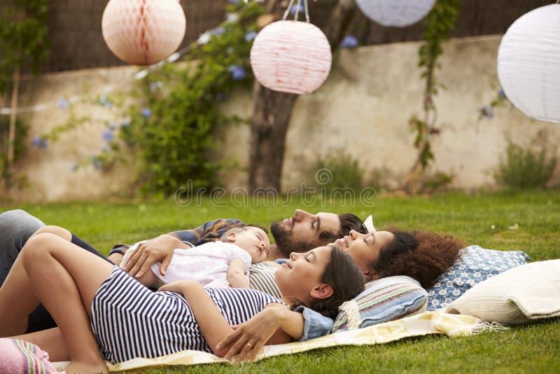 Famiglia con il bambino che si rilassa insieme sulla coperta in giardino immagine stock