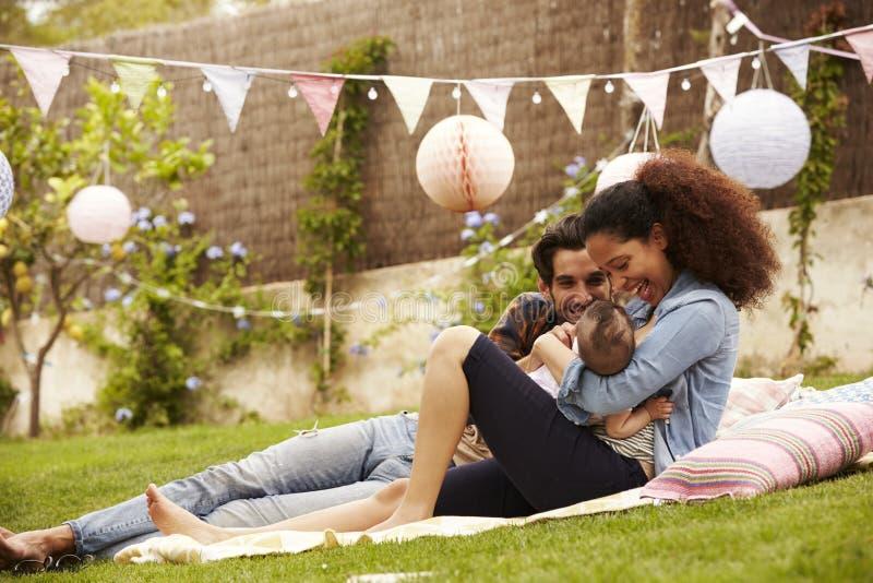 Famiglia con il bambino che si rilassa insieme sulla coperta in giardino fotografia stock