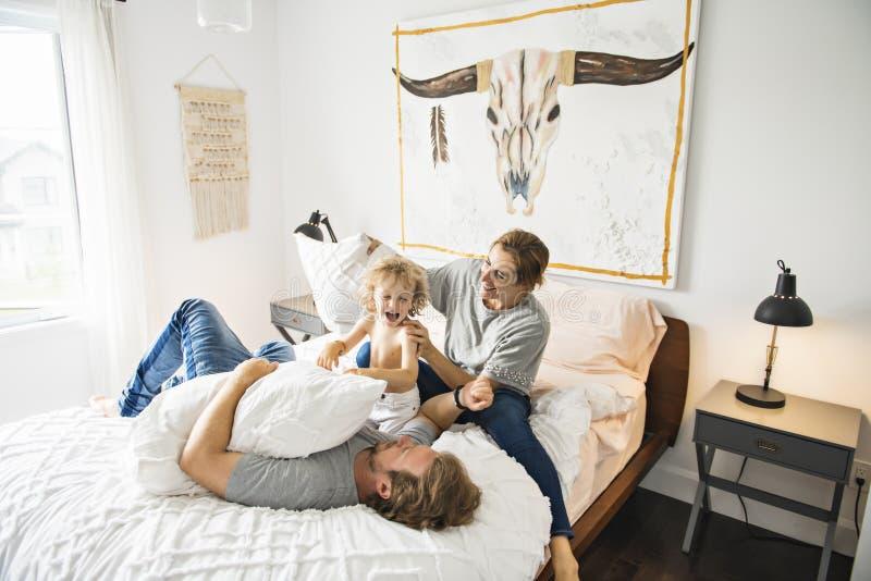 Famiglia con il bambino divertendosi sul letto con la lotta di cuscino fotografia stock