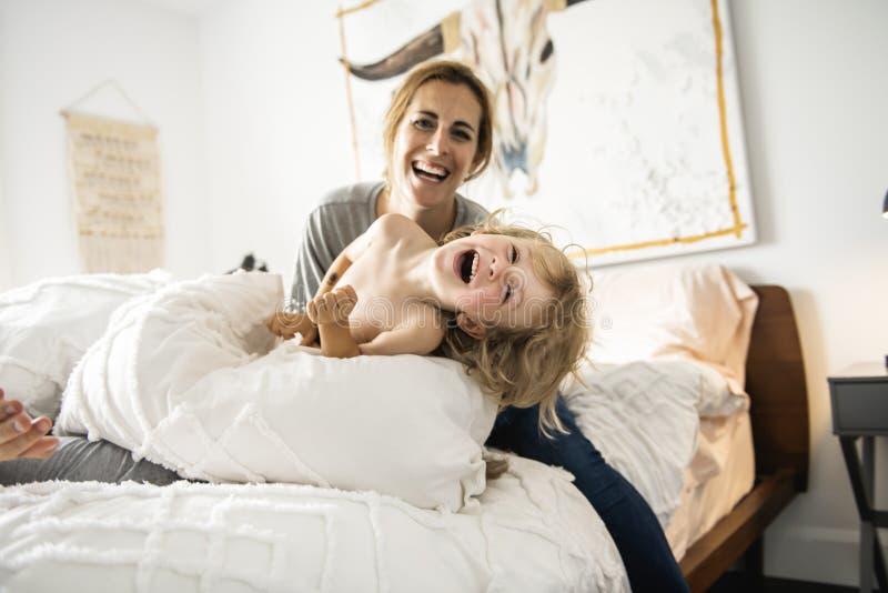 Famiglia con il bambino divertendosi sul letto con la lotta di cuscino immagine stock libera da diritti