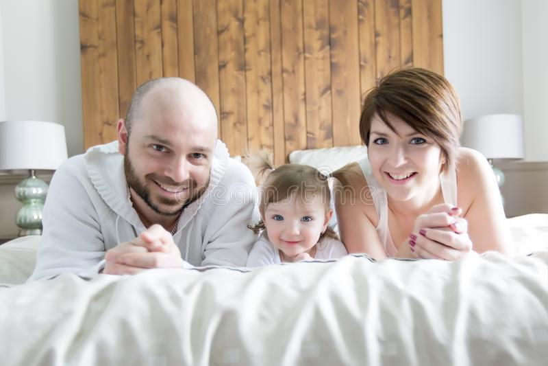 Famiglia con il bambino Genitori felici che giocano con il bambino sul letto immagine stock libera da diritti