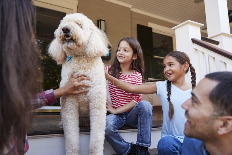 Famiglia con il cane che si siede sui punti di nuova casa sul muoversi nel giorno immagine stock libera da diritti