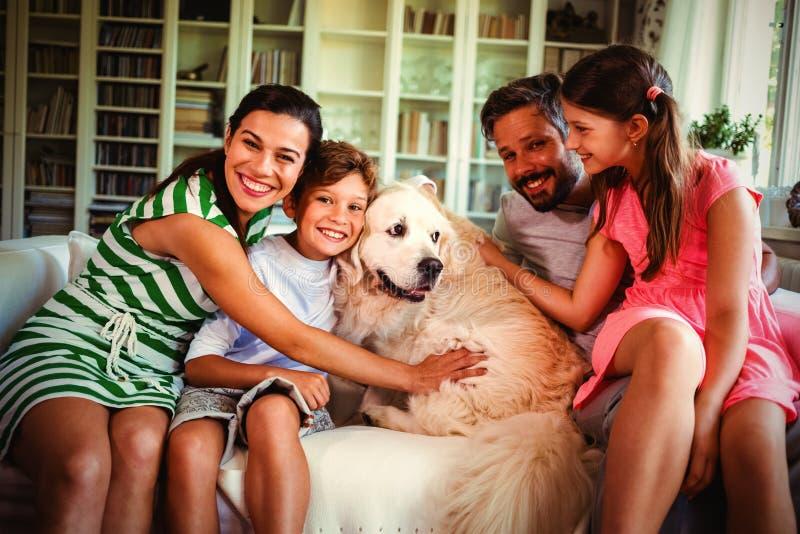Famiglia con il cane che si siede sul sofà in salone immagini stock