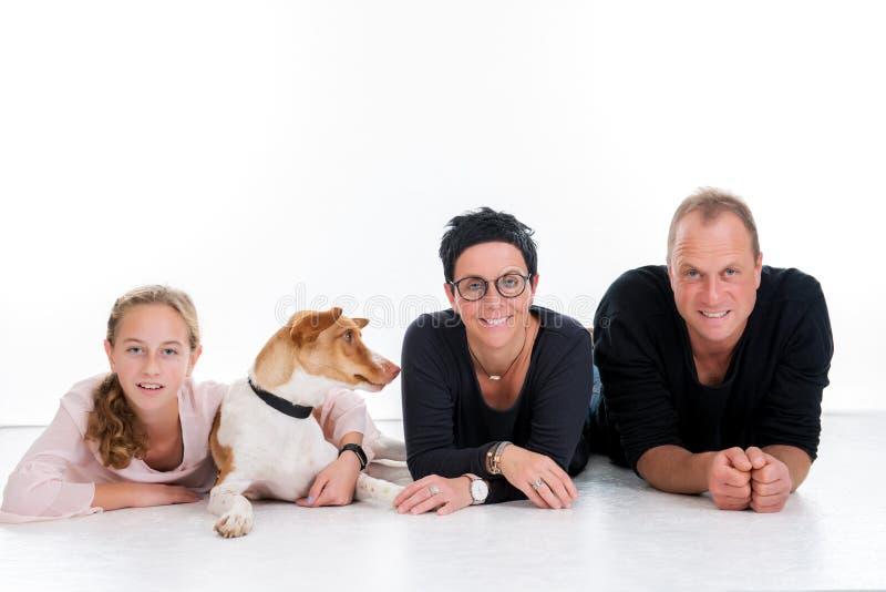 Famiglia con il cane che si trova davanti al fondo bianco fotografia stock