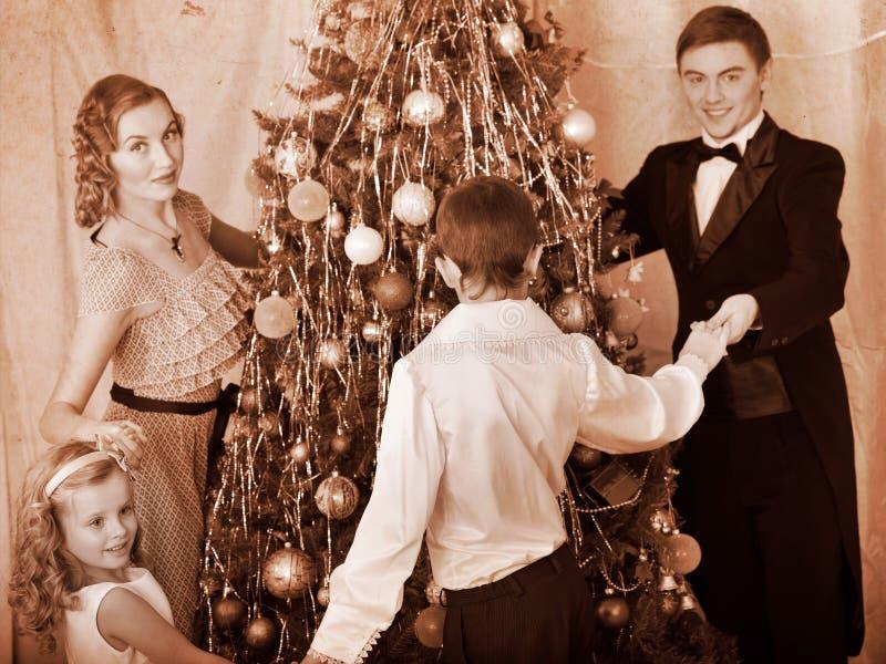 Famiglia con l'albero di Natale di ballo rotondo dei bambini. fotografia stock