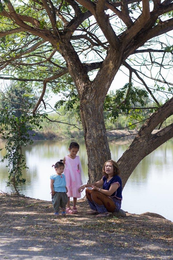 Famiglia con l'albero vicino alla laguna fotografia stock libera da diritti
