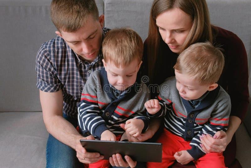 Famiglia con la compressa Mamma, papà e due gemelli dei figli esaminanti compressa che si siede in sofà immagine stock libera da diritti