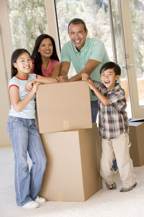 Famiglia con le caselle nel nuovo sorridere domestico immagini stock