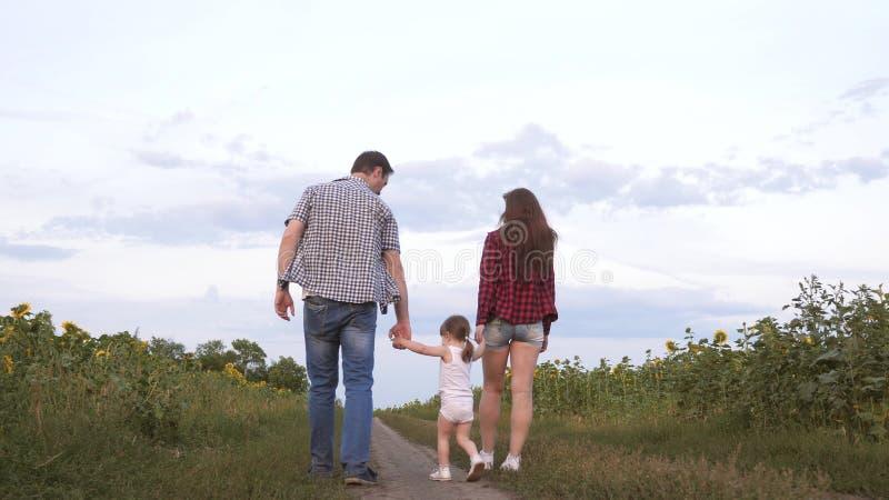 Famiglia con le piccole passeggiate del bambino lungo la strada e le risate accanto al campo dei girasoli Il bambino sta guidando fotografie stock