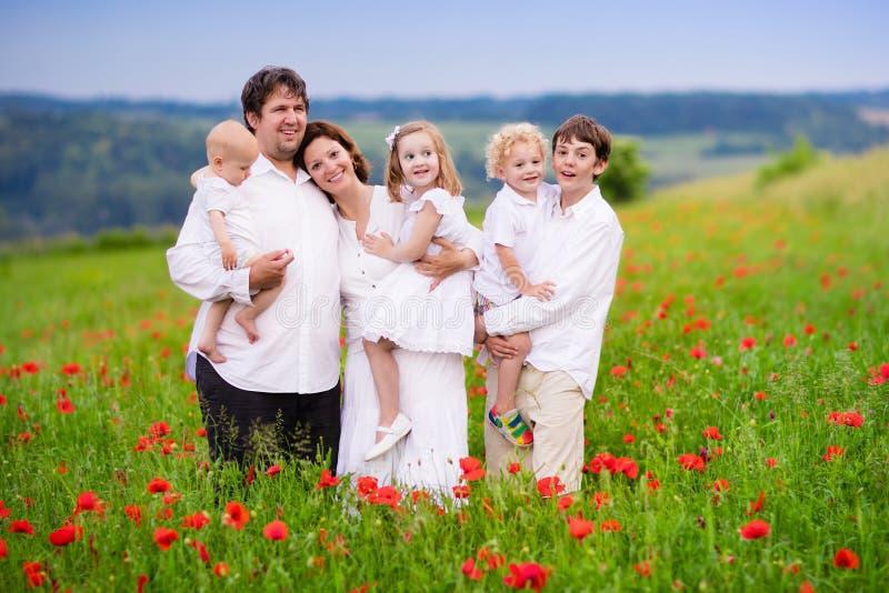 Famiglia con quattro bambini nel giacimento di fiore del papavero fotografie stock