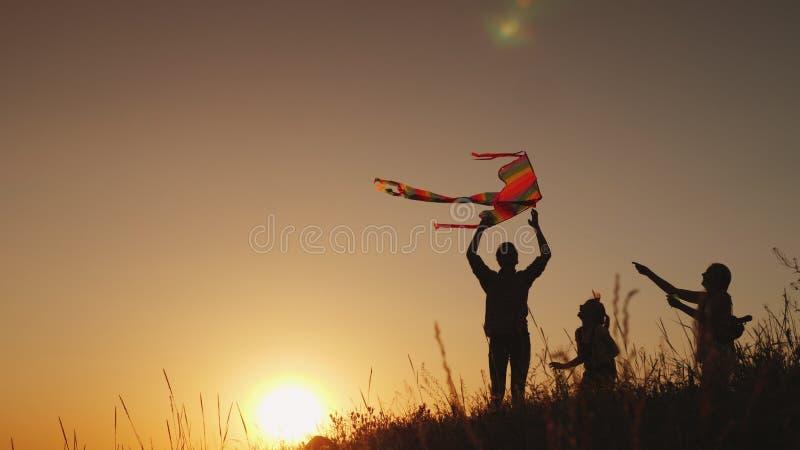 Famiglia con un bambino che gioca con un aquilone In un posto pittoresco al tramonto Attività e vacanza di estate fotografie stock