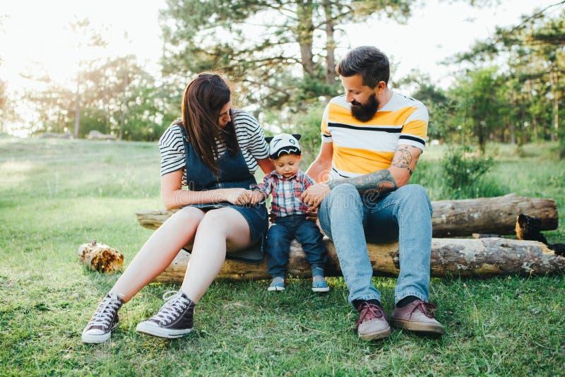 Famiglia dei pantaloni a vita bassa, papà barbuto con i tatuaggi e vestiti alla moda immagine stock libera da diritti