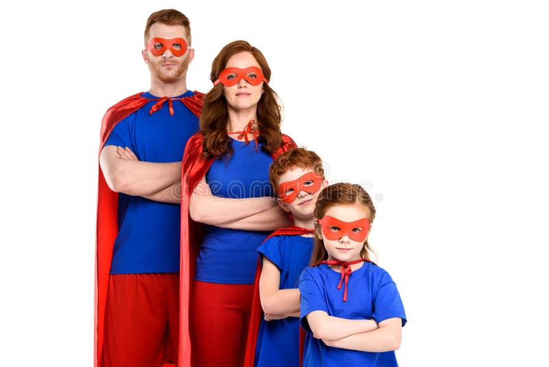 famiglia dei supereroi che stanno con le armi attraversate e che esaminano macchina fotografica immagini stock