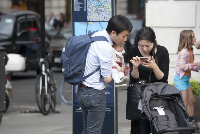 Famiglia dei turisti: padre, madre e bambino in lei armi - guardando nel telefono, provante a determinare l'itinerario immagine stock