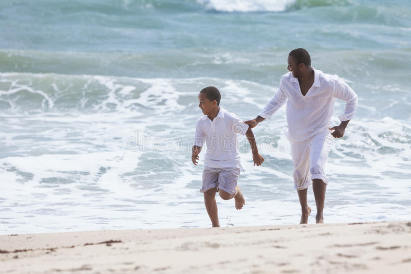 Famiglia del figlio del padre dell'afroamericano sulla spiaggia fotografia stock