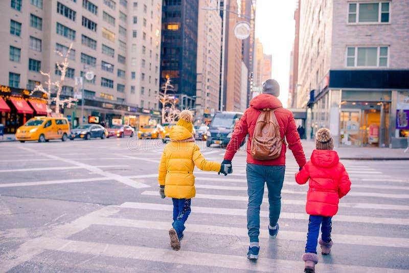 Famiglia del padre e dei bambini sul Times Square durante la loro vacanza in New York immagine stock libera da diritti