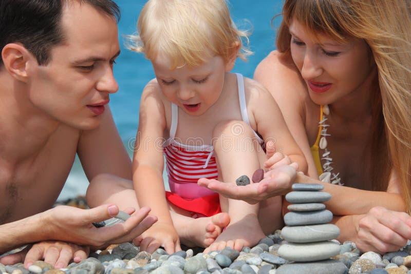 Famiglia del primo piano sul litorale di mare e piramide delle pietre immagini stock