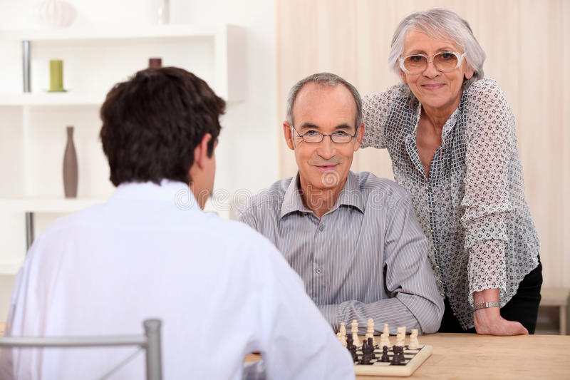 Famiglia dell'adulto che gioca scacchi fotografia stock