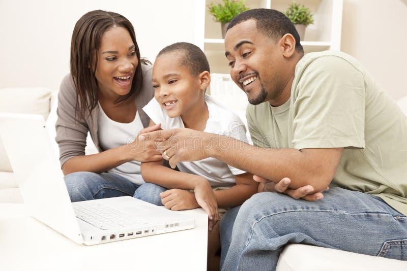 Famiglia dell'afroamericano che per mezzo del computer portatile immagini stock libere da diritti