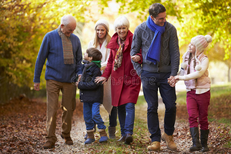 Famiglia della generazione di Multl che cammina lungo Autumn Path immagine stock libera da diritti