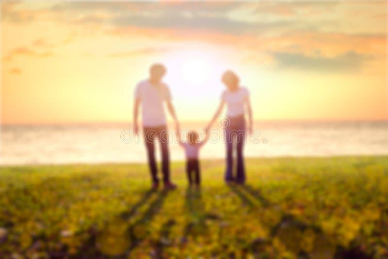 Famiglia della sfuocatura sulla spiaggia immagini stock