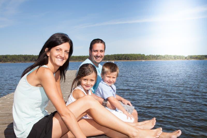 Famiglia di amore che gioca sulla spiaggia sul pontone dell'acqua immagini stock