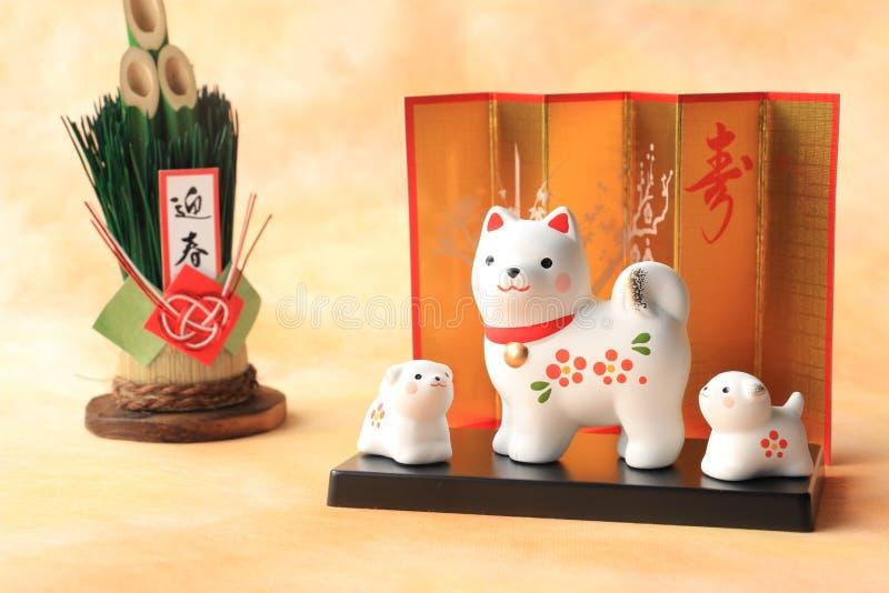 Famiglia di cani giapponese del nuovo anno su fondo di carta tradizionale immagini stock