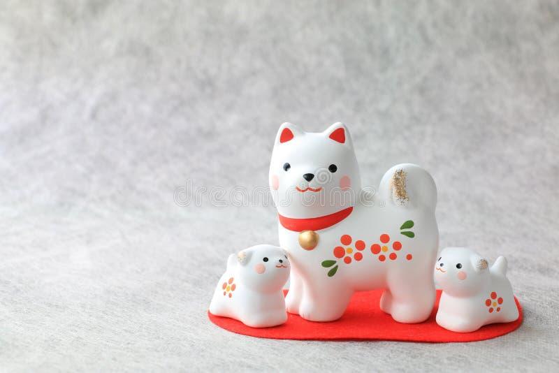 Famiglia di cani giapponese del nuovo anno sul fondo del Libro Bianco immagine stock