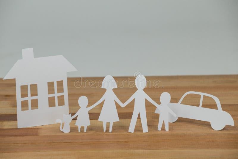 Famiglia di carta del ritaglio con la casa e l'automobile fotografia stock libera da diritti