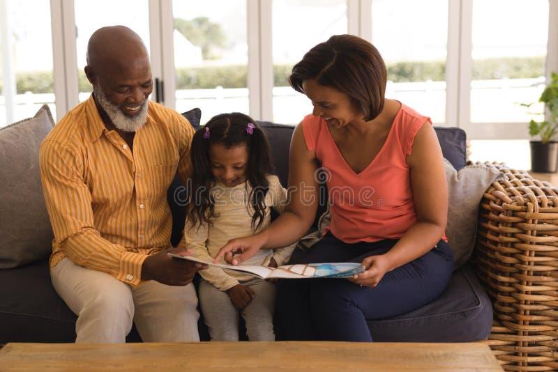 Famiglia di diverse generazioni che legge un libro di storia in salone immagini stock