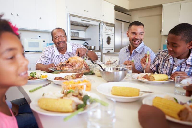 Famiglia di diverse generazioni che si siede intorno alla Tabella che mangia pasto immagini stock libere da diritti