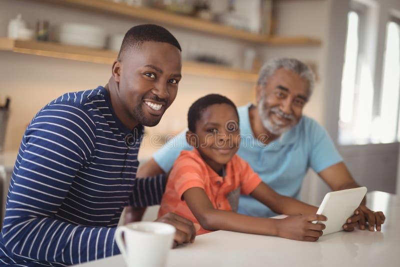 Famiglia di diverse generazioni felice facendo uso della compressa digitale in cucina fotografie stock