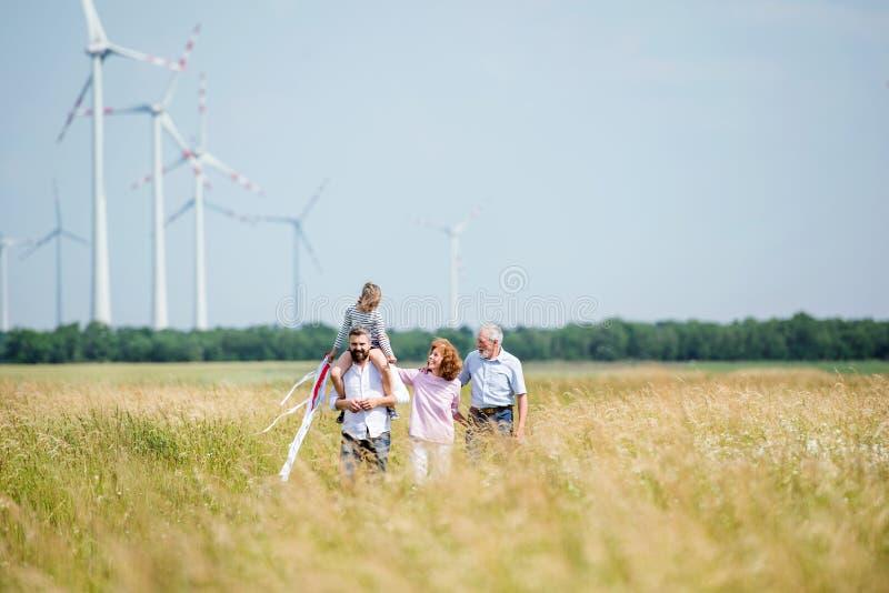 Famiglia di multinazionali che cammina sul campo in un parco eolico fotografia stock