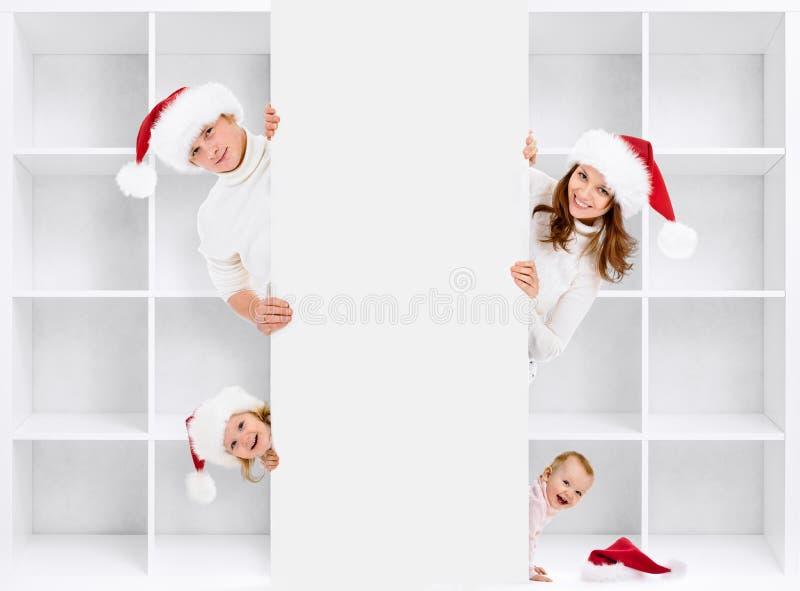 Famiglia di Natale in cappelli di Santa con la scaffalatura fotografie stock libere da diritti