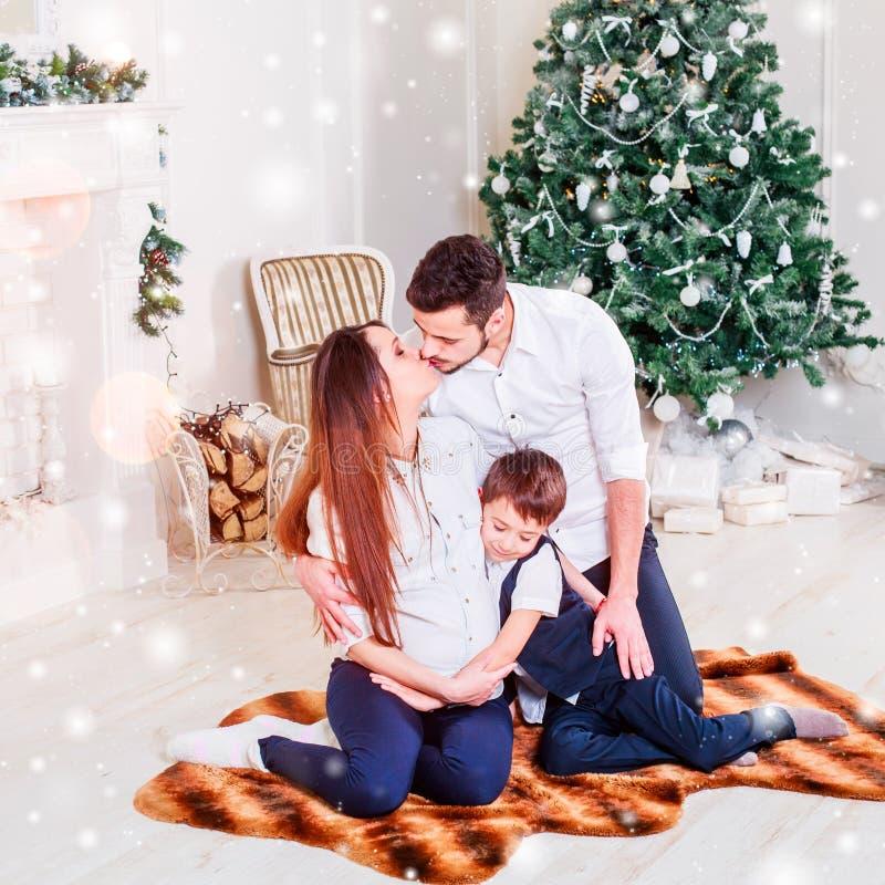 Famiglia di Natale che sorride e che bacia vicino all'albero di natale Salone decorato dall'albero di Natale e dal contenitore di fotografia stock libera da diritti